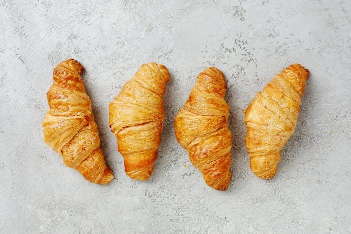 Croissants auf einem strukturierten grauen Hintergrund.