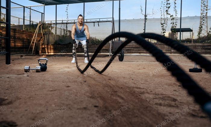Man doing exercise with ropes, workout, crossfit