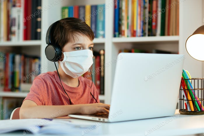 Child wearing face mask learning at home. Young student wearing