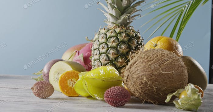 Panoramic video around composition of fresh natural ripe exotic fruits on a woodwn gray table on a