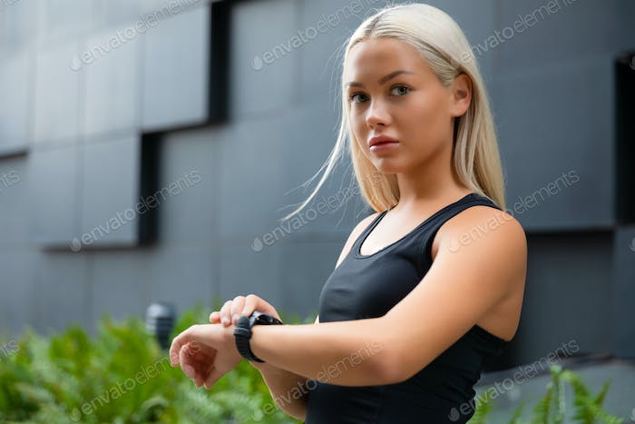 Young blonde woman checking her fitness smart watch device in city