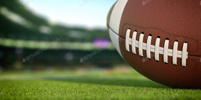 American football ball on grass of football arena
