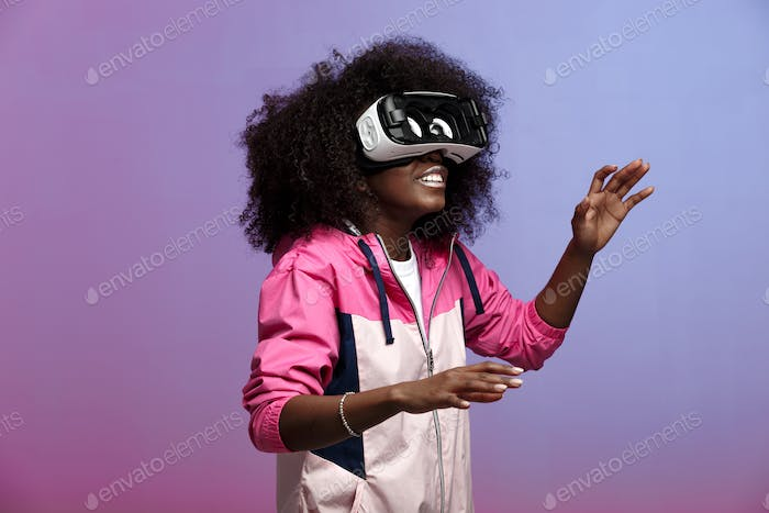 Mod young brown-haired curly girl dressed in the pink sports jacket uses the virtual reality glasses