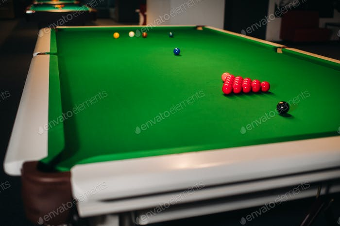 placing snooker balls on a green billiard table