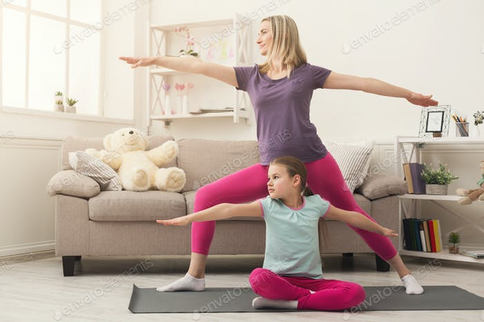 Young woman and child daughter training at home