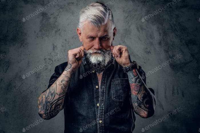 Brutal and aged biker in retro style clothing poses in dark background