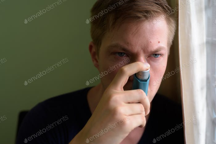 Young handsome man using asthma inhaler at home