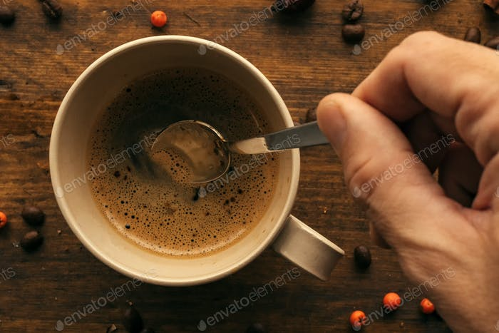 Hand steering coffee in a cup with spoon