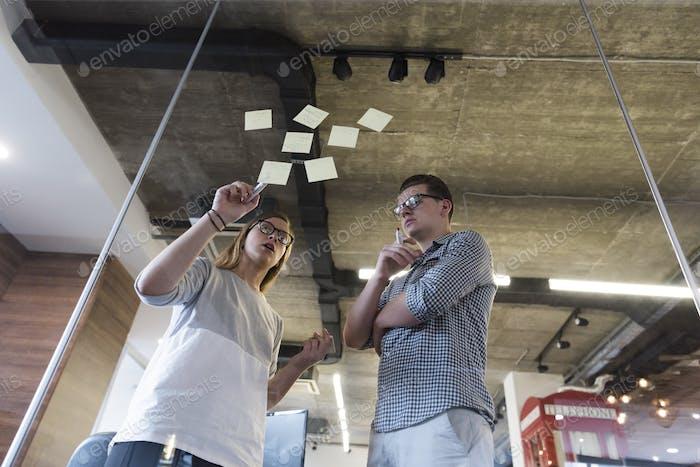 junges Paar im modernen Büro Interieur Schreiben Notizen auf Aufkleber