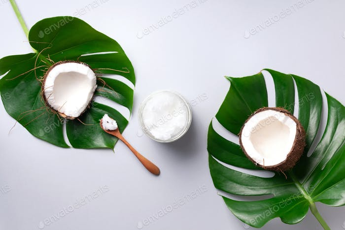 Coconut oil and ripe coconuts, tropical palm and monstera leaves on grey background with copy space