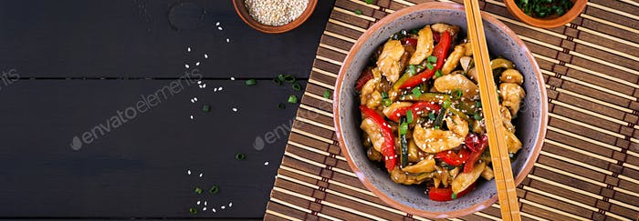 Stir fry chicken, zucchini, sweet peppers and green onion. Banner. Top view. Asian cuisine
