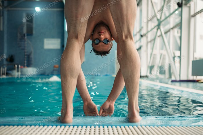 Swimmer in goggles ready to start in swimming pool