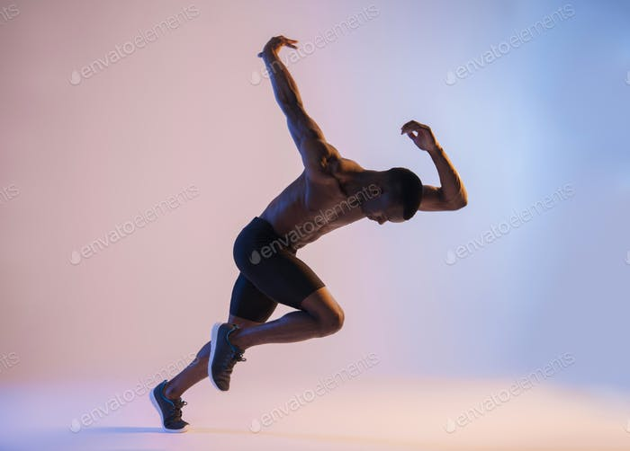 Muscular Shirtless African-American man sprinting in red and blue light
