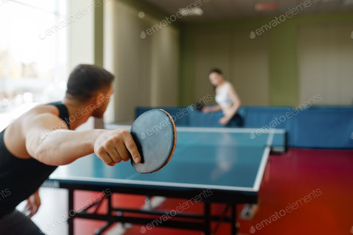 Man and woman playing ping pong, focus on racket