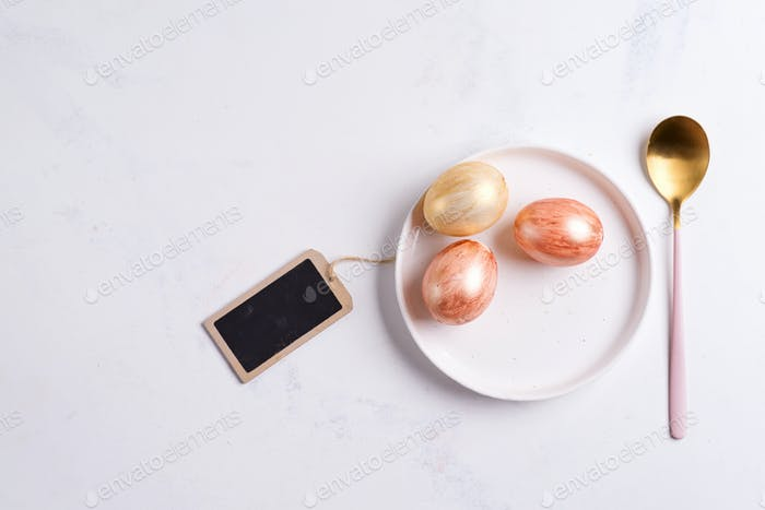 Greeting card with handmade painted bright eggs on a plate and golden spoon on a light grey marble