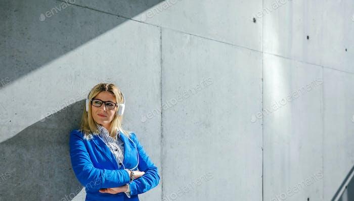 Mujer de negocios con auriculares posando