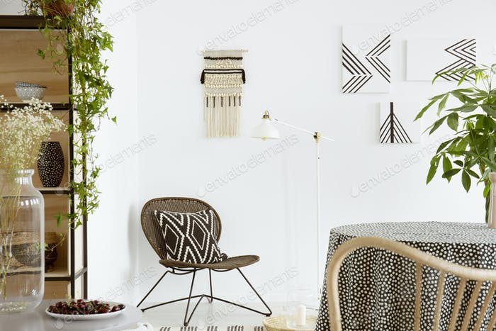 Patterned cushion on chair and plant on table in white boho livi
