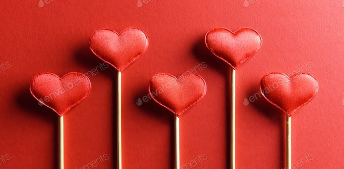 Red textile hearts on wooden sticks closeup