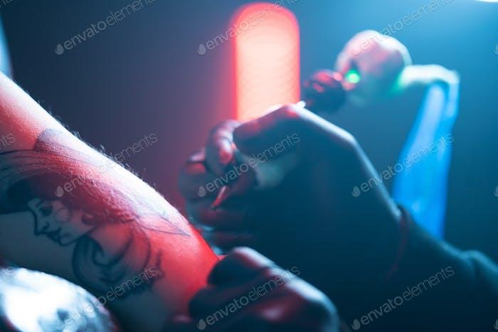 Extreme Nahaufnahme Tattoo Nadel und Haut im Schönheitssalon
