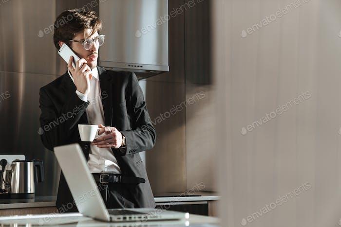 Foto von jungen Geschäftsmann im Gespräch auf Handy während des Kaffeetrinks