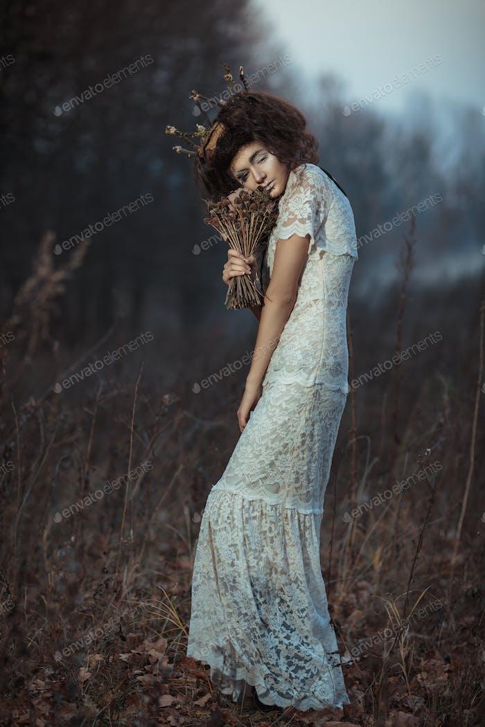Junges Mädchen in einem weißen Spitzenkleid, eine Krone aus Zweigen mit einer Bouque