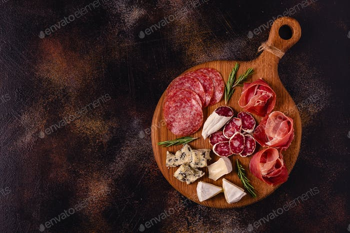 Serving board with meat and cheese snacks.