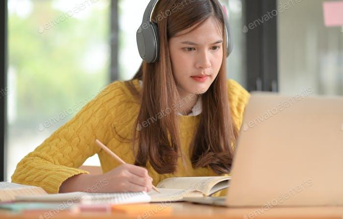 Teenager-Mädchen tragen Kopfhörer, um online zu studieren und Vorträge zu halten.