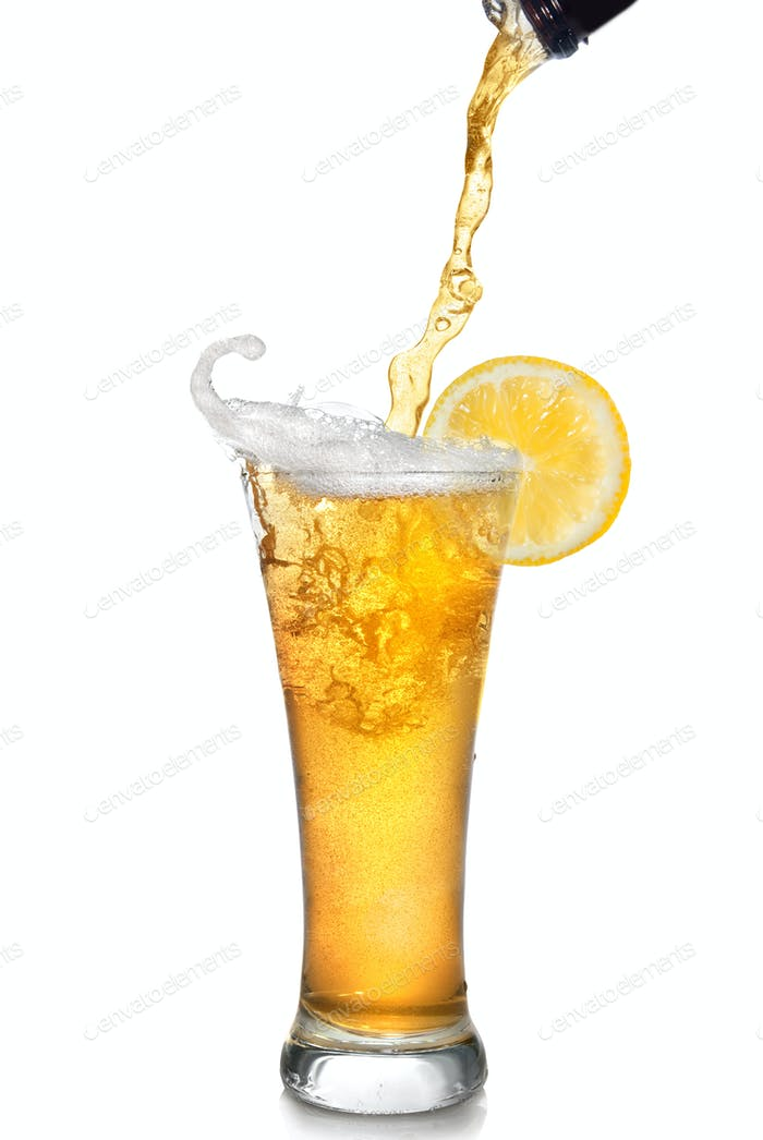 Beer pouring from bottle into glass with lemon isolated on white