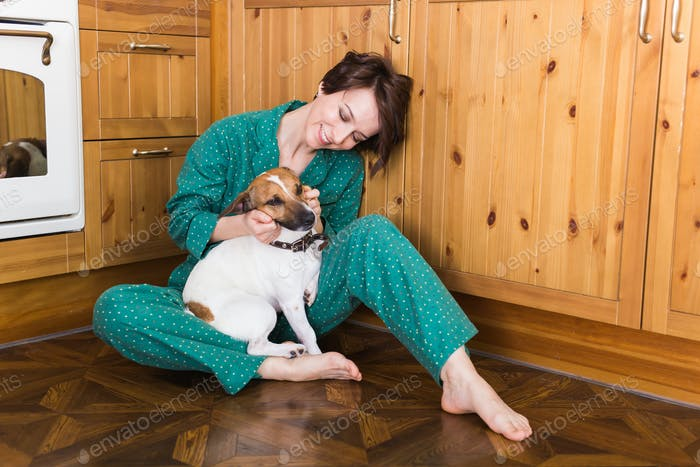 Young beautiful woman at home with her cute dog. Quarantine, isolation, coronavirus pandemic world