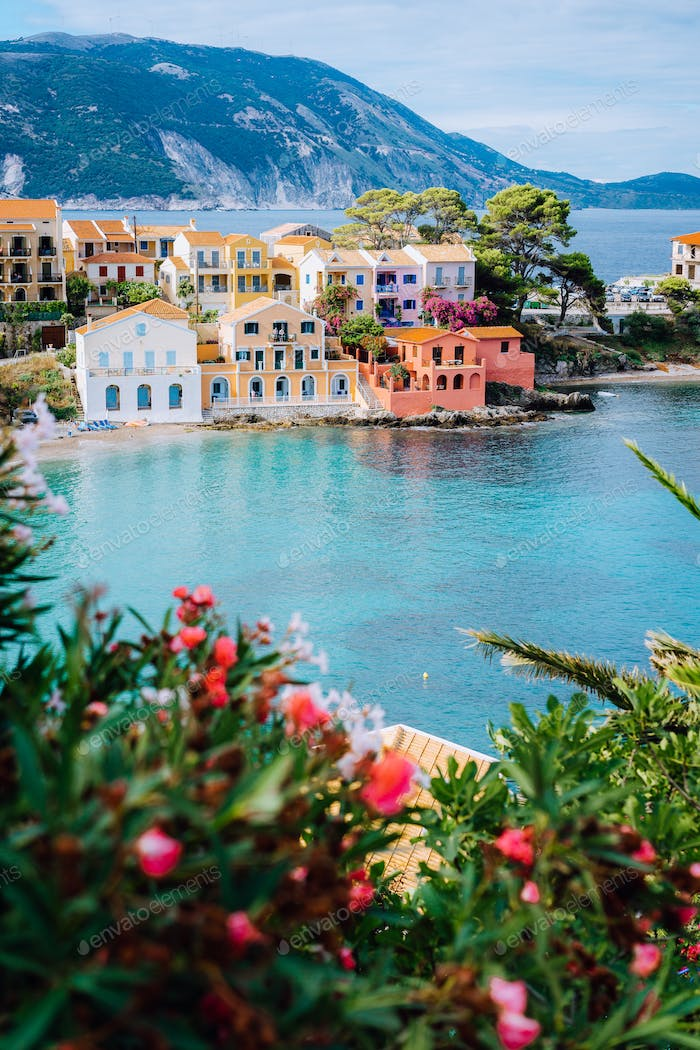 Beautiful colorful southern houses and blue bay of Mediterranean sea with some red flowers on
