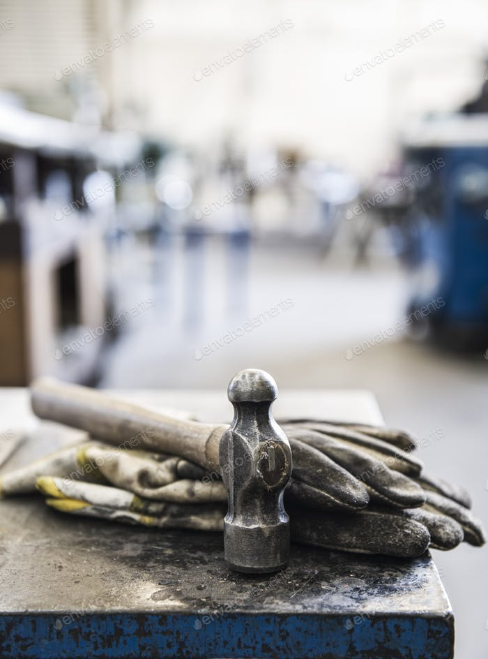 Closeup still life of gloves and a heavy duty hammer in a sheet metal factory.