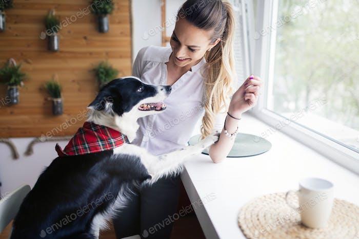 Schöne Frau glücklich während der Zeit mit ihrem Hund zu Hause