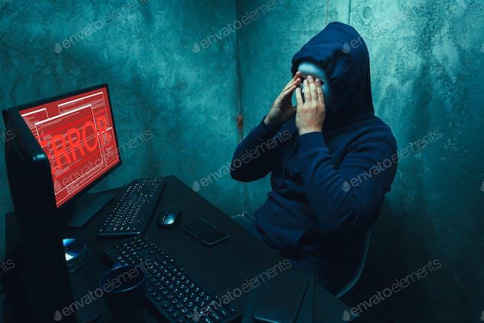Hacker anónimo con máscara facial trabajando en computadora en cuarto oscuro