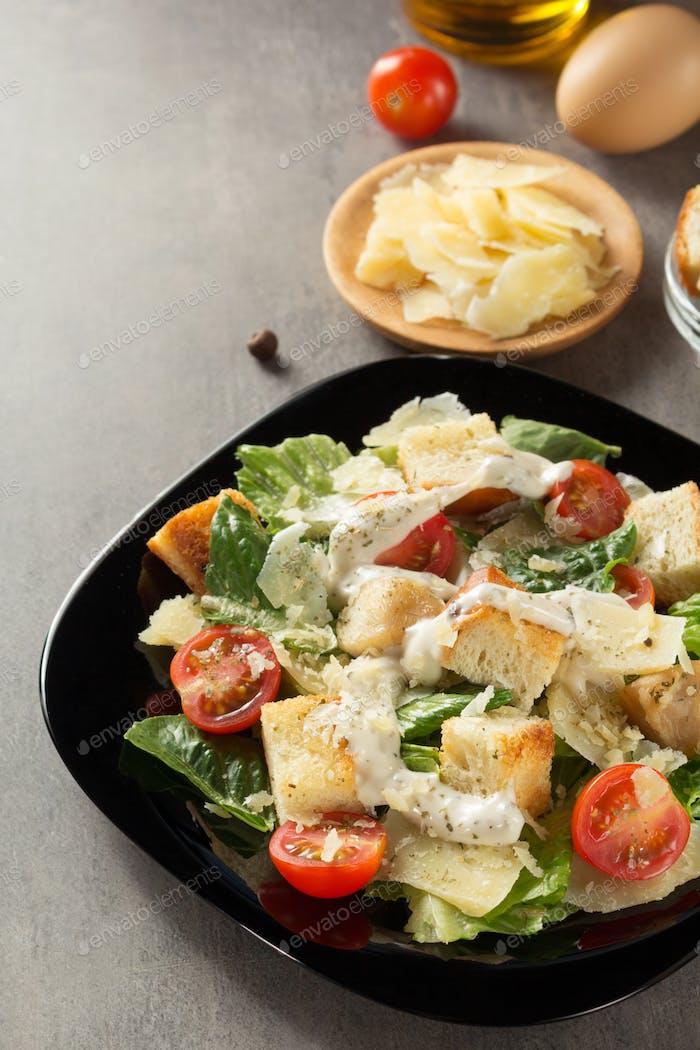 caesar salad and ingredients at table