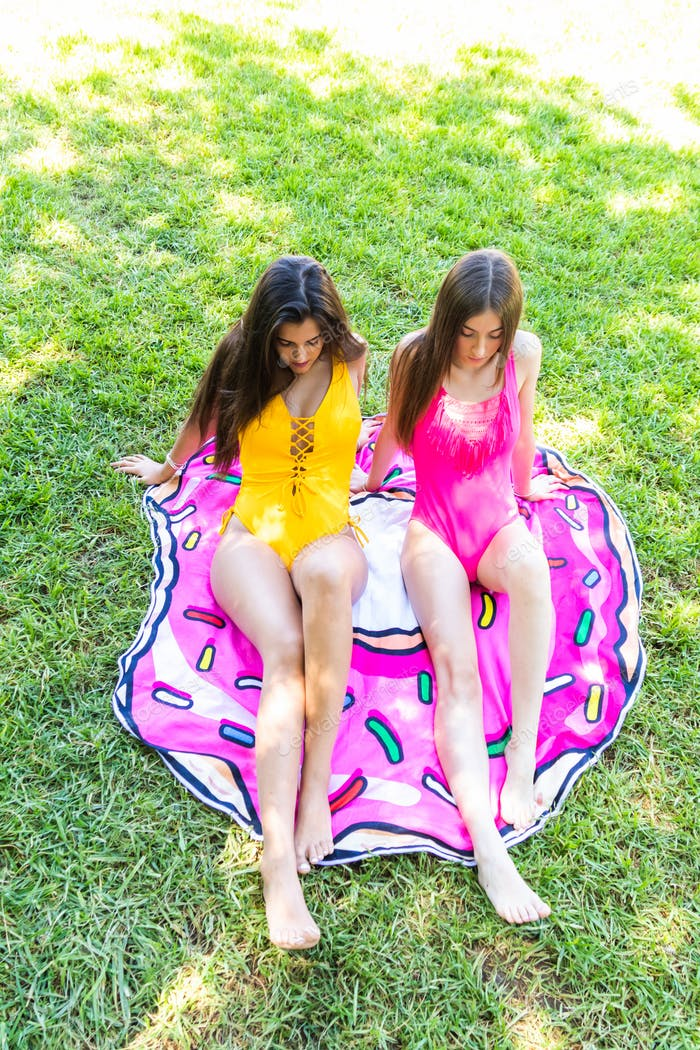 Two young girls in swimsuits having fun sitting on the pool lawn
