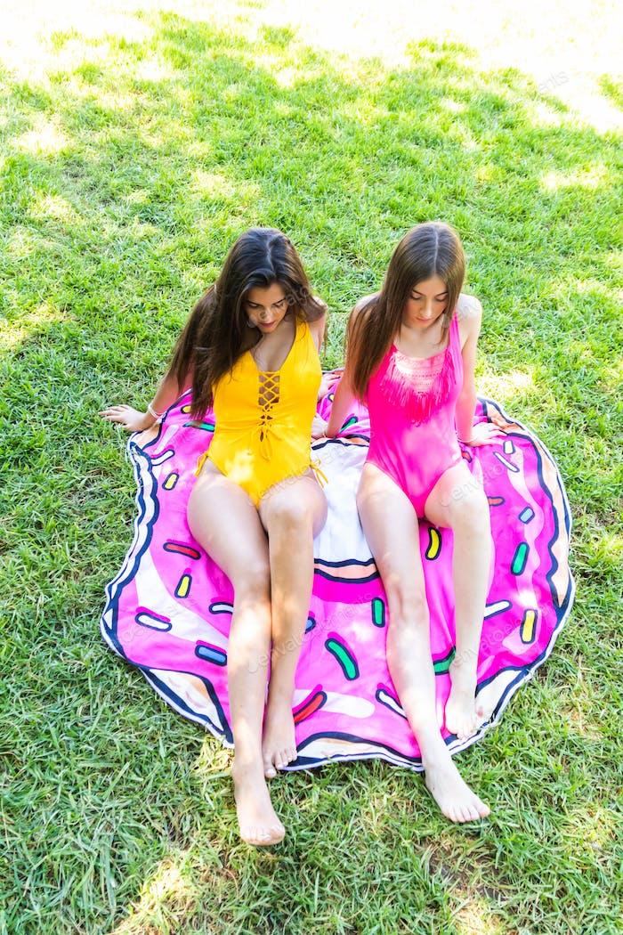 Zwei junge Mädchen in Badeanzügen mit Spaß sitzen auf der Poolwiese