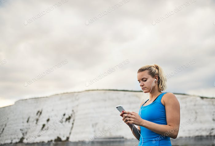 Young sporty woman runner with earphones and smartphone standing on the beach.