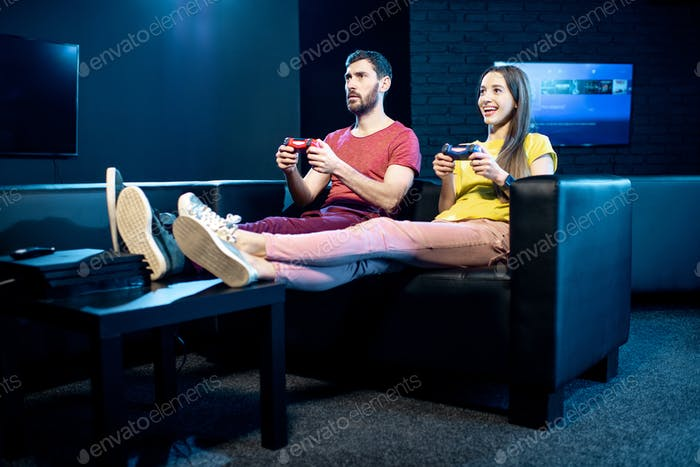 Couple playing video games with gaming console in the club