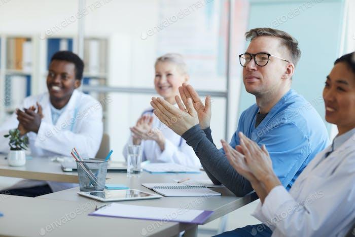 Gruppe von Ärzten applaudiert bei der Sitzung