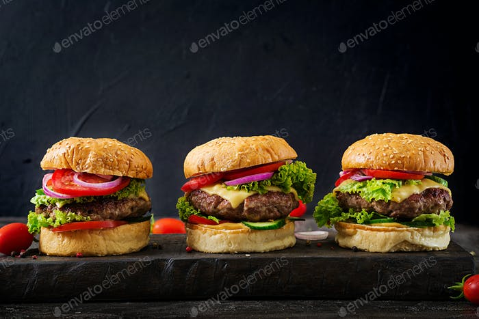 Three hamburger with beef meat burger and fresh vegetables on dark background. Tasty food.