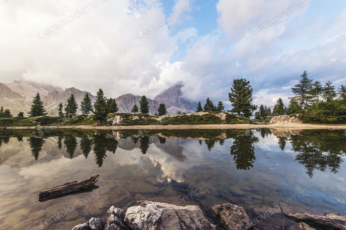 Fascinating reflections of the Dolomites mountains in lake Limedes at Sunset