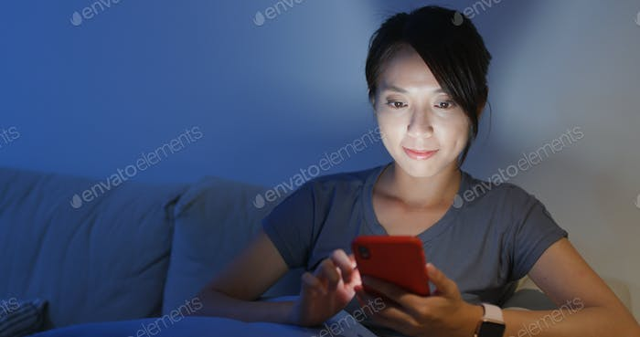 Housewife use of smart phone for working at home in the evening
