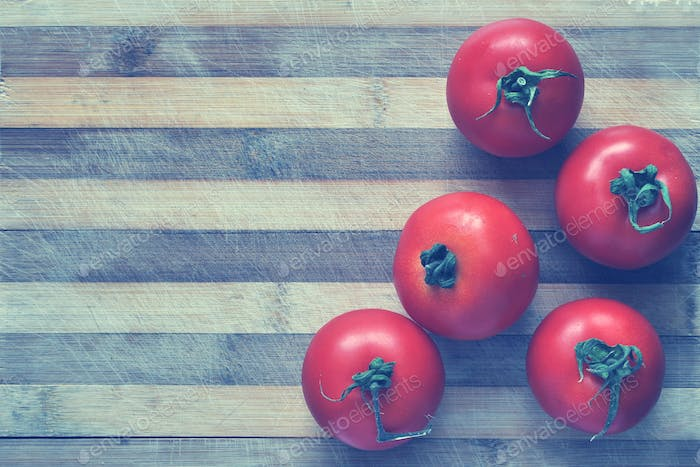Red tomatoes on a cutting board. Toned