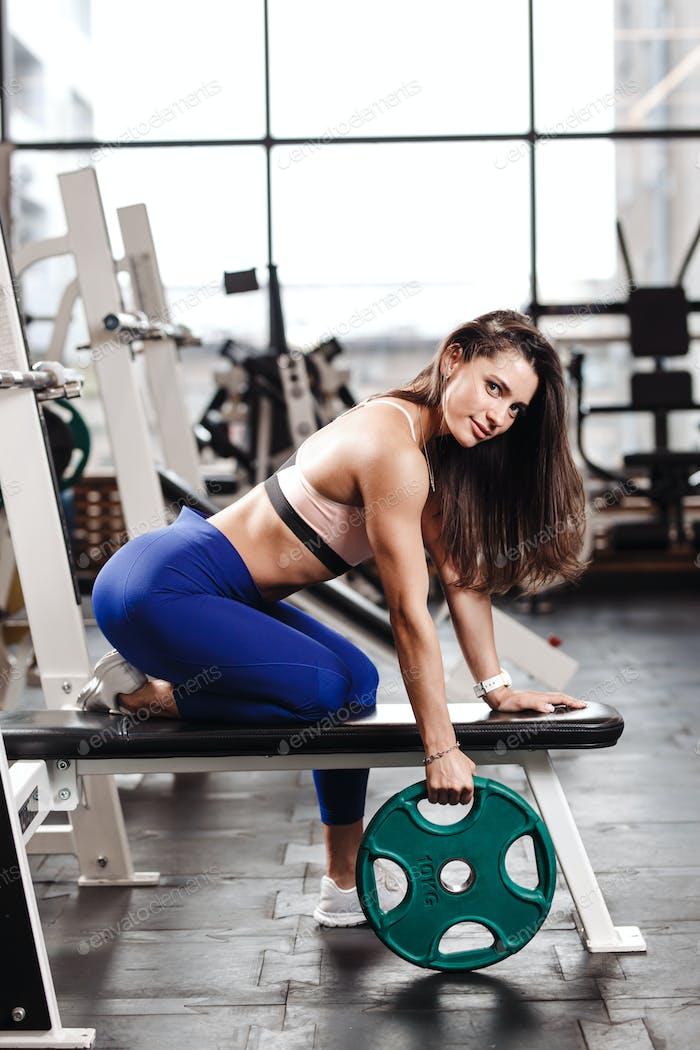 Junge athletische Brünette Mädchen in einer Sportbekleidung gekleidet sitzt auf der Bank mit der Platte in der
