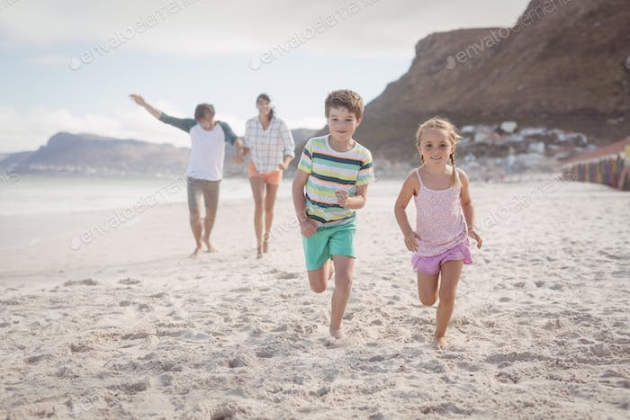 Siblings running on sand with parents in background