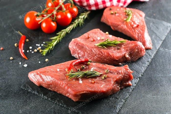 Rohes Fleisch. Rohes Rindfleischsteak auf einem schwarzen Brett mit Kräutern und Gewürzen. Nahaufnahme