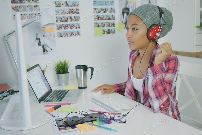 Trendy worker in headphones working