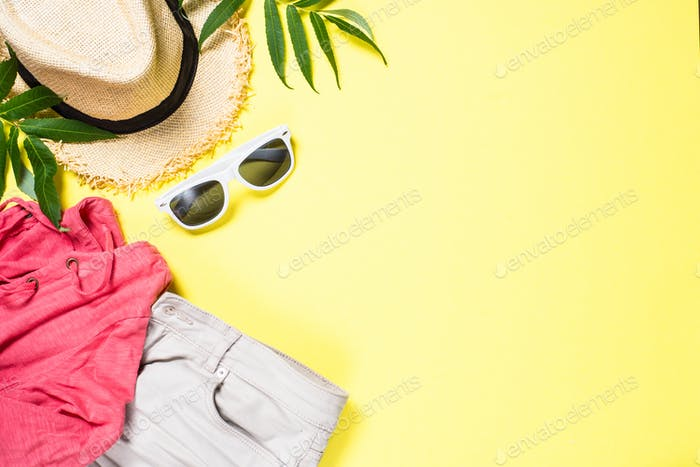 Woman summer cloth set - hat, top, shorts and sunglasses on yellow