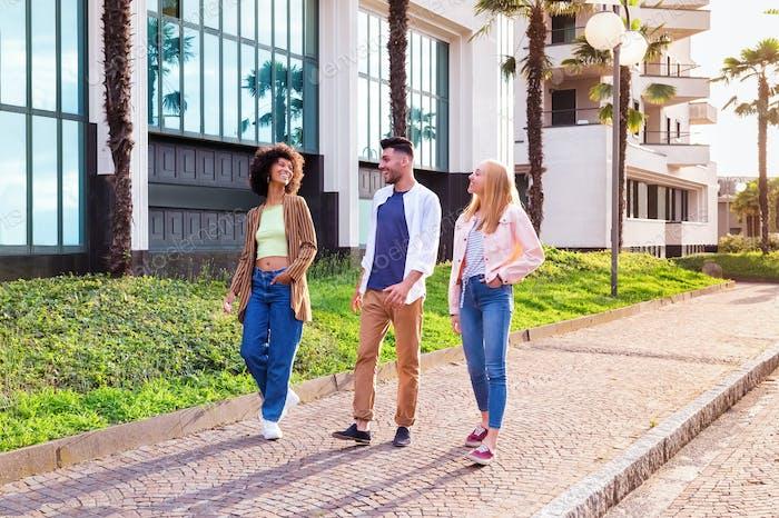 Happy diverse friends walking on street