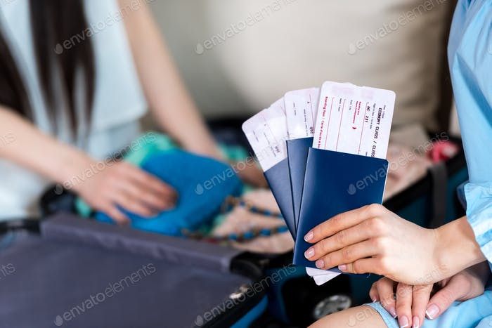 Close-up partial view of woman holding passports and tickets, getting ready to travel concept